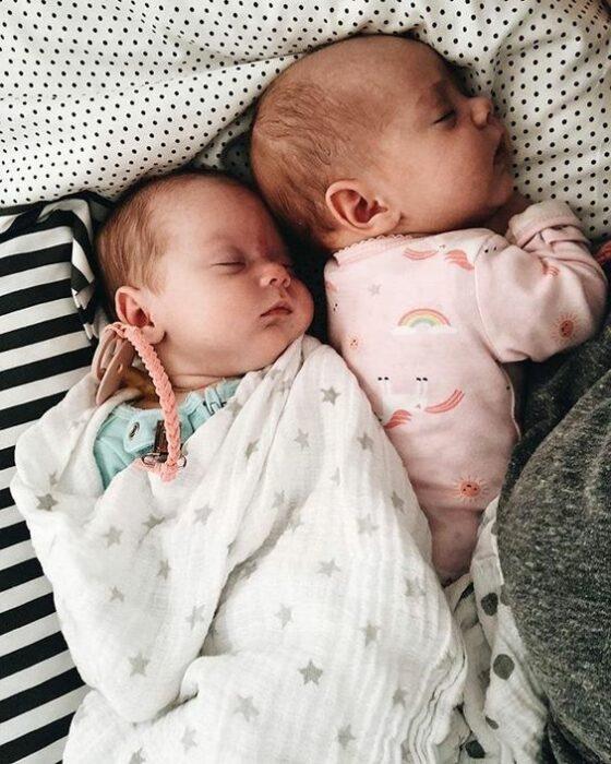 Bebés acostados boca arriba en una cama con cobija a rayas blanca con negro