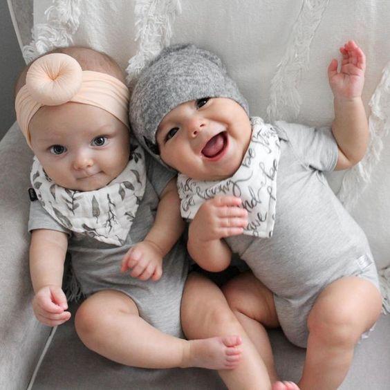 Bebés sentados en sillón con pañaleros grises, pañuelos blancos y una diadema en la cabeza