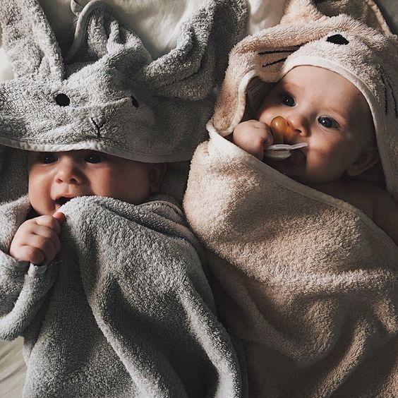 Bebés acostados boca arriba en una cama con toallas de elefante y osito