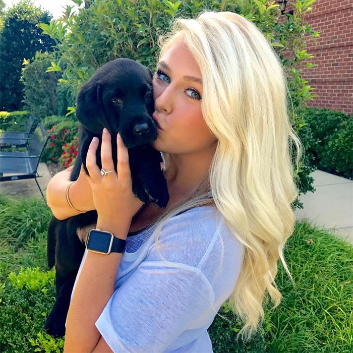 Chica sujetando a su perrito labrador mientras lo está besando
