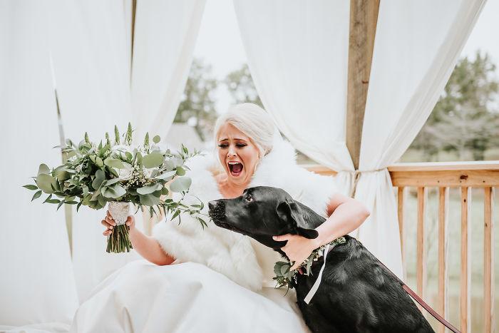 Chica vestida de novia intentando contener a su perro de que mordiera el ramo