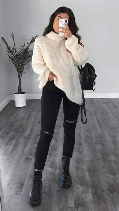 Chica usando jeans negros rasgados, botines y bolsa de mano negra con suéter holgado color hueso de cuello de tortuga