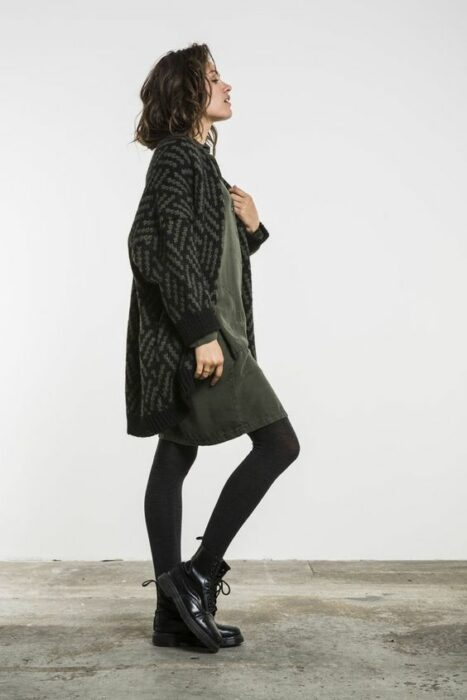 Girl wearing ankle boots, black mayas and military green dress with long black and gray cardigan