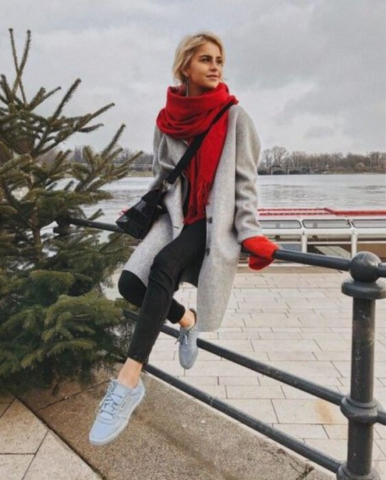 Girl wearing gray tennis shoes, black jeans, black sweater, long light gray coat and red scarf