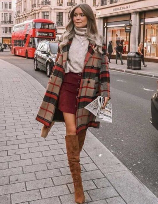 Girl wearing camel high boots, wine colored mini skirt, beige high neck blouse and plaid cape