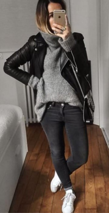Girl wearing faded black jeans, white tennis shoes, slouchy gray sweater and black leather jacket