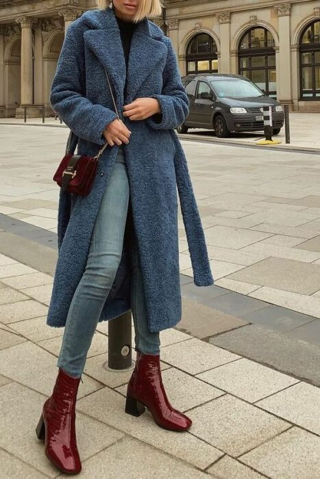 Girl wearing jeans, black blouse, long blue fur coat, with a bag and burgundy boots