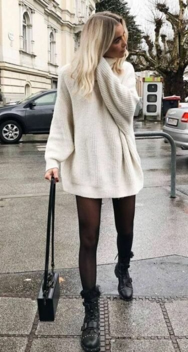 Girl wearing black ankle boots, stockings and handbag, with off-white knitted jersey blouse