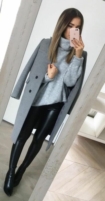 Girl wearing black leggings and ankle boots, with sky blue high neck sweater and long gray coat