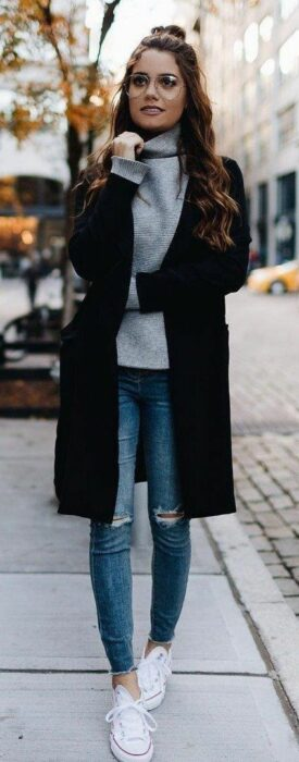 Girl wearing jeans with white tennis shoes, high neck sweater and long black coat