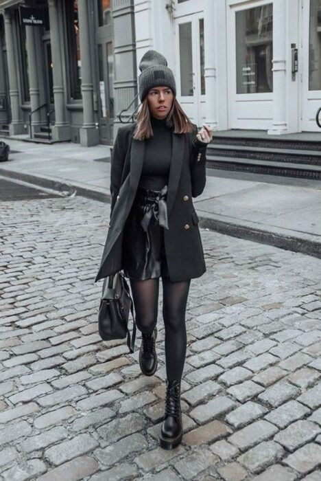 Girl wearing ankle boots, with stockings, leather mini skirt, high neck sweater and long coat with handbag all in black, with rat gray hat