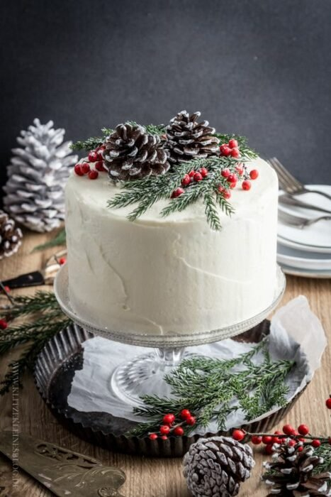 Pastel de Navidad de vainilla con decorado de piñas de pino y cerezas
