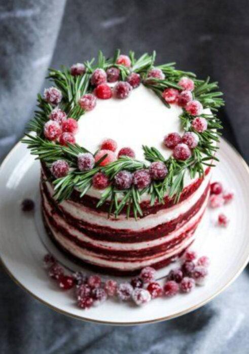 Pastel de Navidad de red velvet con relleno de vainilla y decorado de frutos rojos