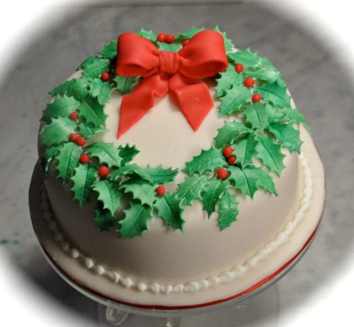 Pastel de Navidad de vainilla con decorado de corona de navidad y moño rojo