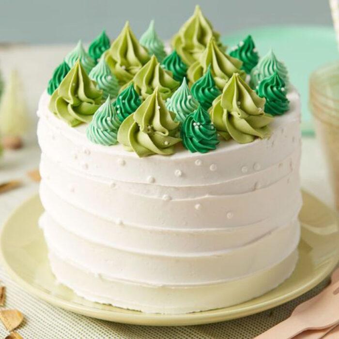 Pastel de Navidad de vainilla con decorado de pinos de diferentes verdes