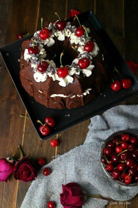 Pastel de Navidad de chocolate con relleno de crema batida con decorado de cerezas