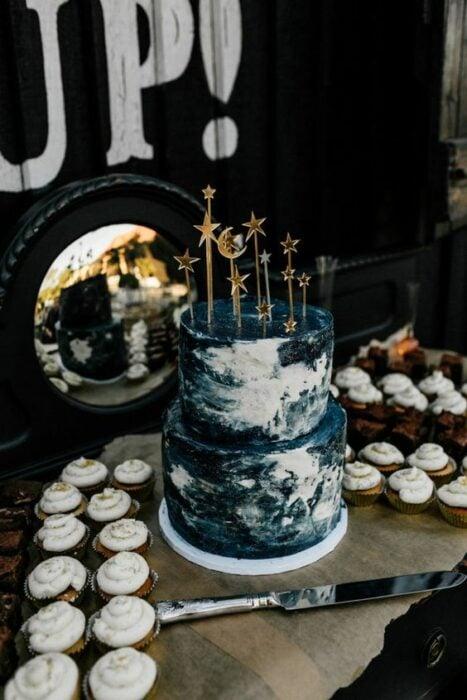 Pastel de dos pisos decorado en colores oscuros con betún pastelero inspirado en la galaxia; Pasteles inspirados en la galaxia