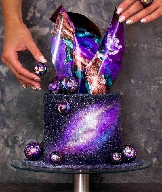 Pastel decorado en tonos morados y negro con esferas galacticas; Pasteles inspirados en la galaxia