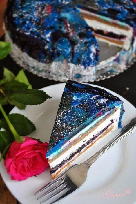 Rebanada de pastel rellena con queso crema y decorada con betún en tonos azules; Pasteles inspirados en la galaxia