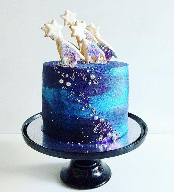 Pastel de un piso decorado con betún de crema en colores azul y morado con estrellas de chocolate blanco; Pasteles inspirados en la galaxia