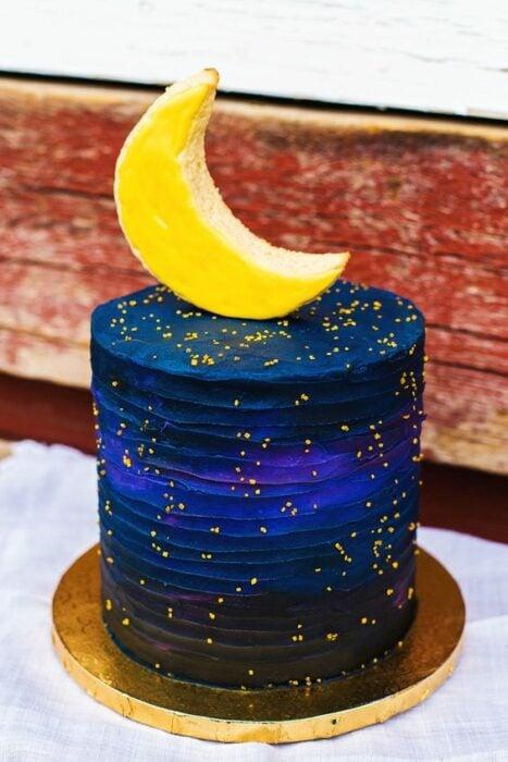 Pastel decorado con una media luna, con betún y chispas amarillas; Pasteles inspirados en la galaxia