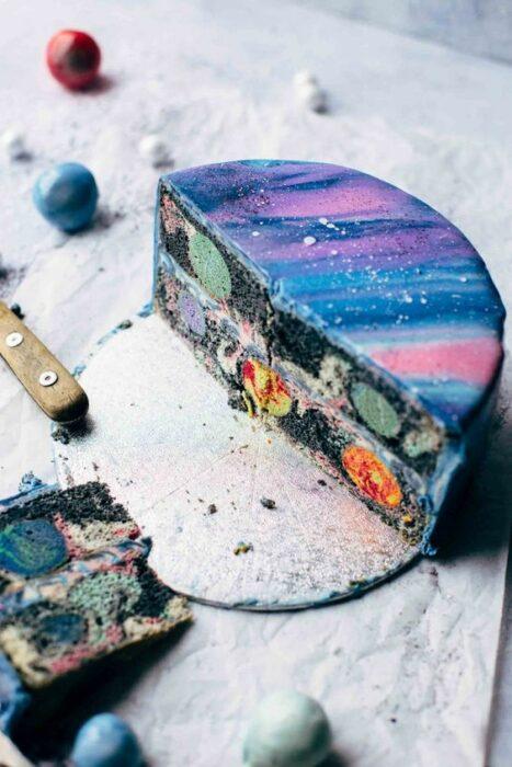Pastel partido a la mitad decorado con betún en tonos rosas y morados; Pasteles inspirados en la galaxia