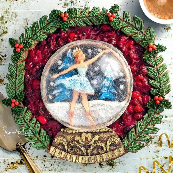 Pay con cobertura crujiente con decoración de bailarina de ballet en una bola de nieve con orillas con decoración de ramas comestibles de pino