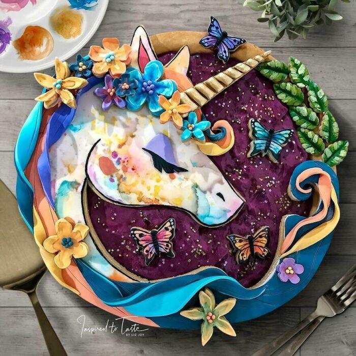 Pay de moras con cobertura de decoración de unicornio y mariposas