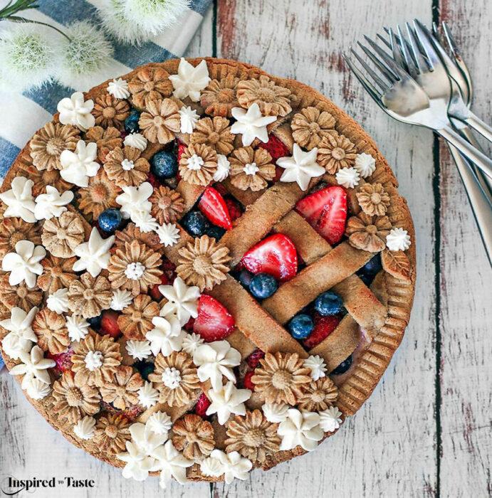 Pay de calabaza con cobertura crujiente de masa, fresas, moras y flores comestibles blancas