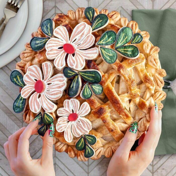 Pay con cobertura crujiente con decoración de flores comestibles blancas y hojas verdes