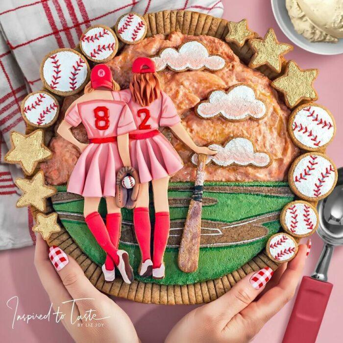 Pay de calabaza con decoración de chica jugadoras de beisbol con pelotas y estrellas al rededor