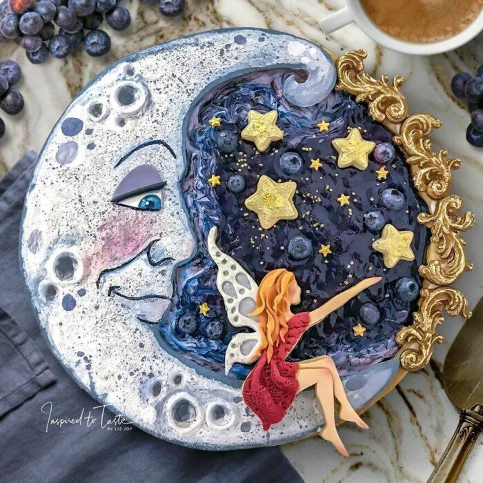 Pie de moras con cobertura en forma de luna con un hada sentada tocando las estrellas