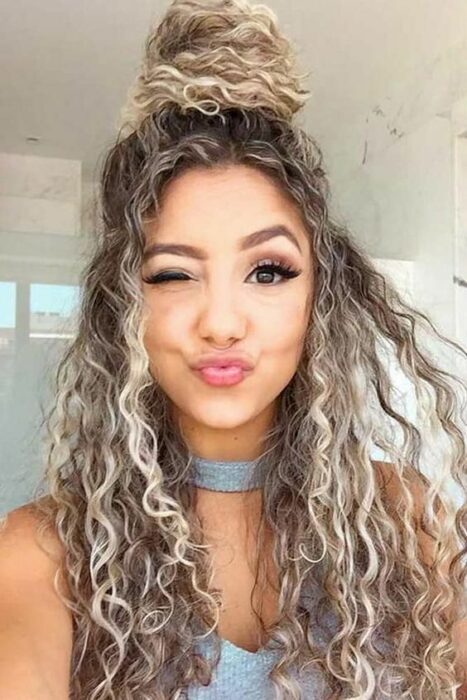 Girl with curly hair combed in high bun; Hairstyles for curly hair girls