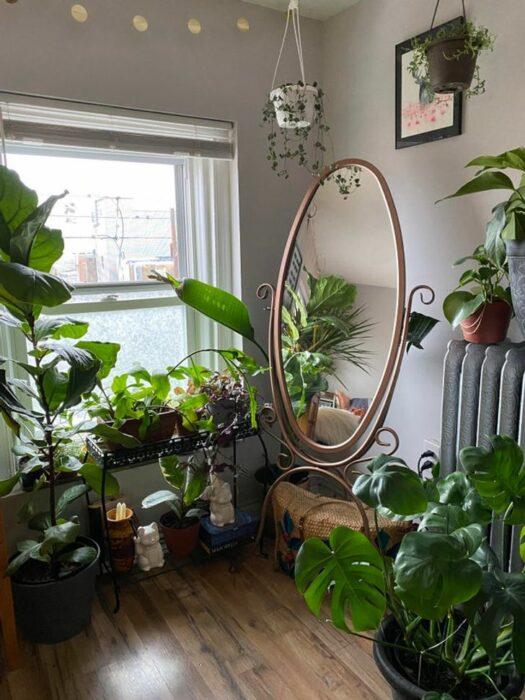 Habitación blanca con ventana grande con cortinas blancas y un espejo de cuerpo completo de forma ovalada y muchas plantas decorativas en el piso