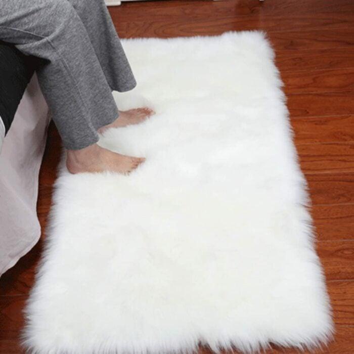 Persona colocando sus pies en un tapete peludo de color blanco