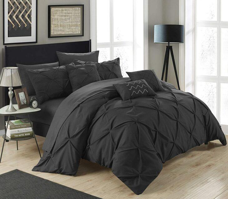 Cobertor de color negro colocado en una recamara con colores grices