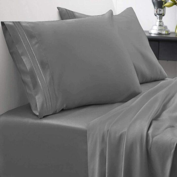 Cama cubierta con unas sabanas de color gris con almohadas y sabana de cajón