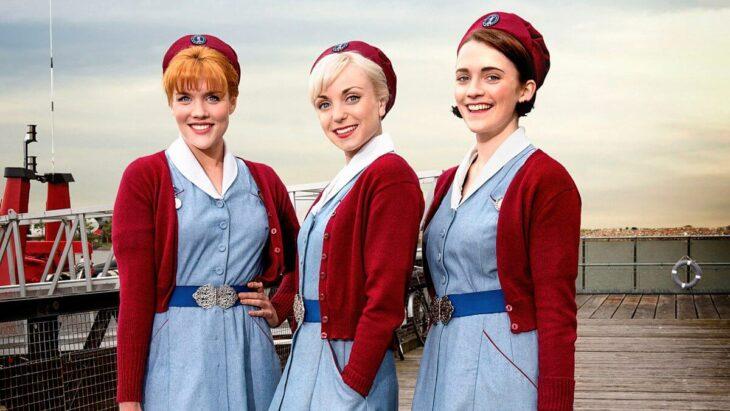 Escena de la serie Call the Midwife,trío de amigas llevando vestido azul y suéter rojo