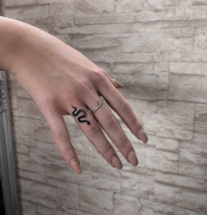 Tattoo of a small snake in the area of the ring finger