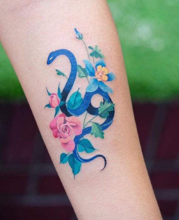Snake tattoo in blue ink, and flowers on the forearm area