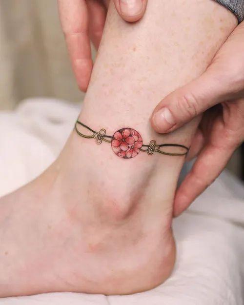 Tatuaje en el tobillo de amuleto asiático color rosa con cadena dorada