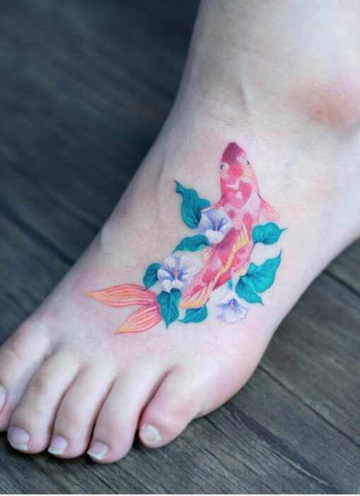 Koi fish in between comb tattoo with white flowers and green leaves