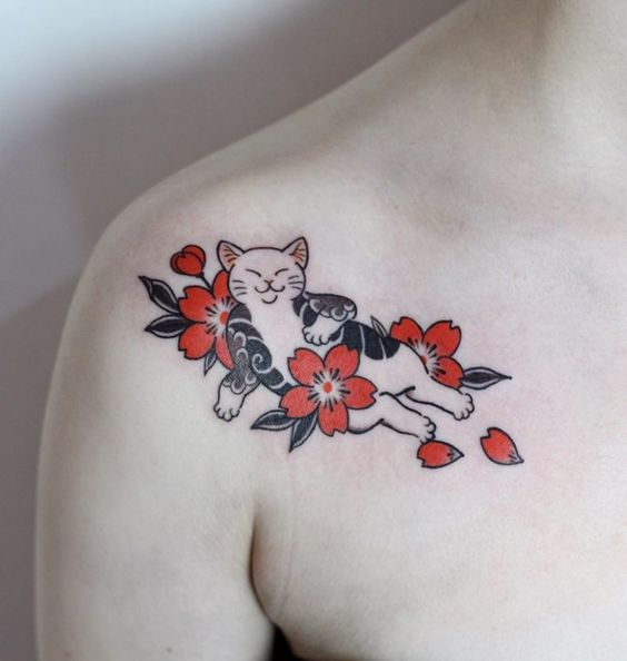 Tatuaje en la clavícula de gatito blanco acsotado rodeado de flores de cerezco rojas
