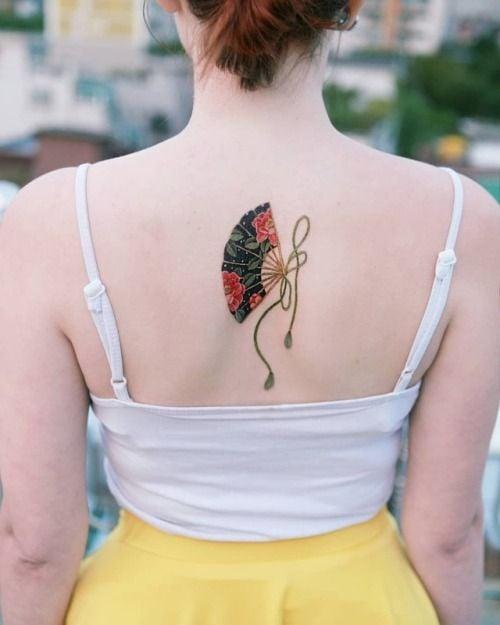 Tatuaje en la espalda de abanico asiático color negro y rojo