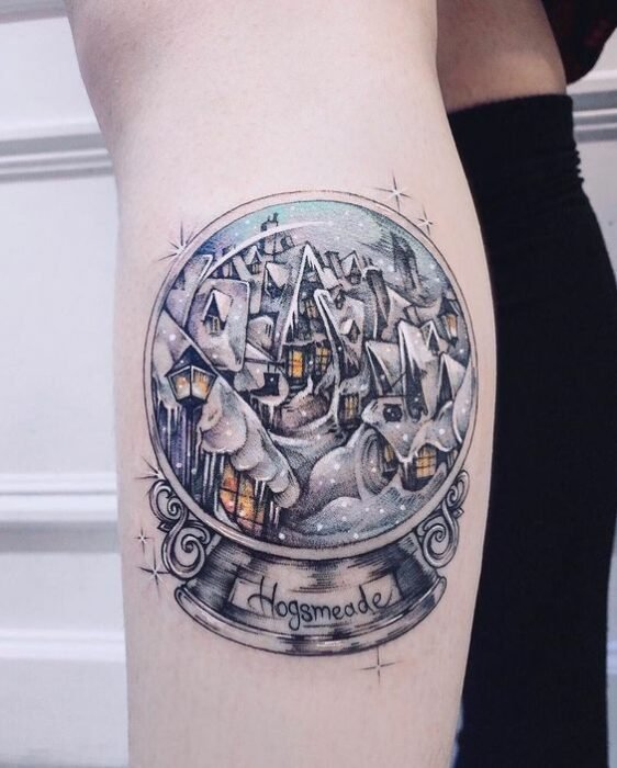 Chica con tatuaje de bola de cristal inspirada en Harry Potter; Tatuajes miniatura para las que aman la Navidad