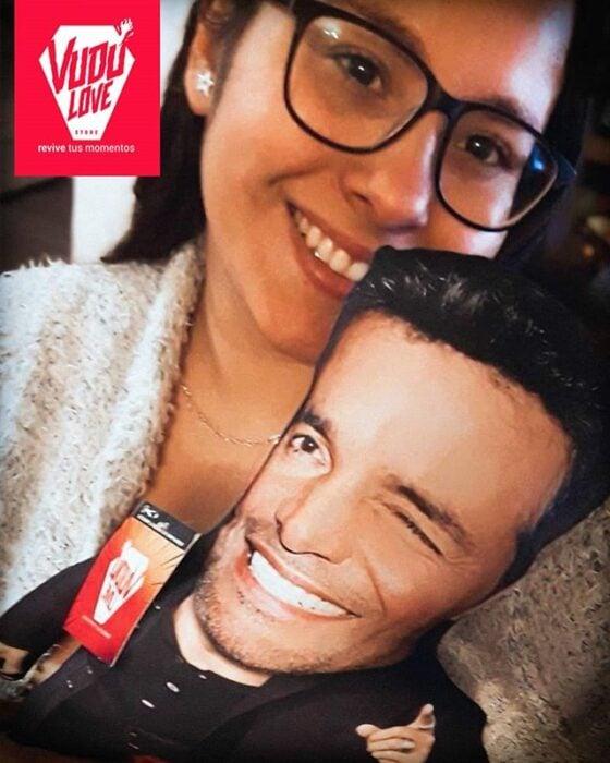 Chica con gafas negras sonríe mientras sostiene un peluche Chayanne