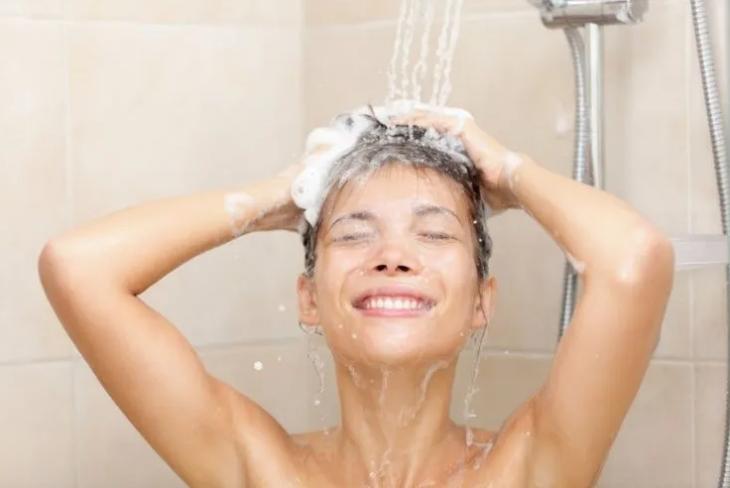 Chica bañando con agua caliente