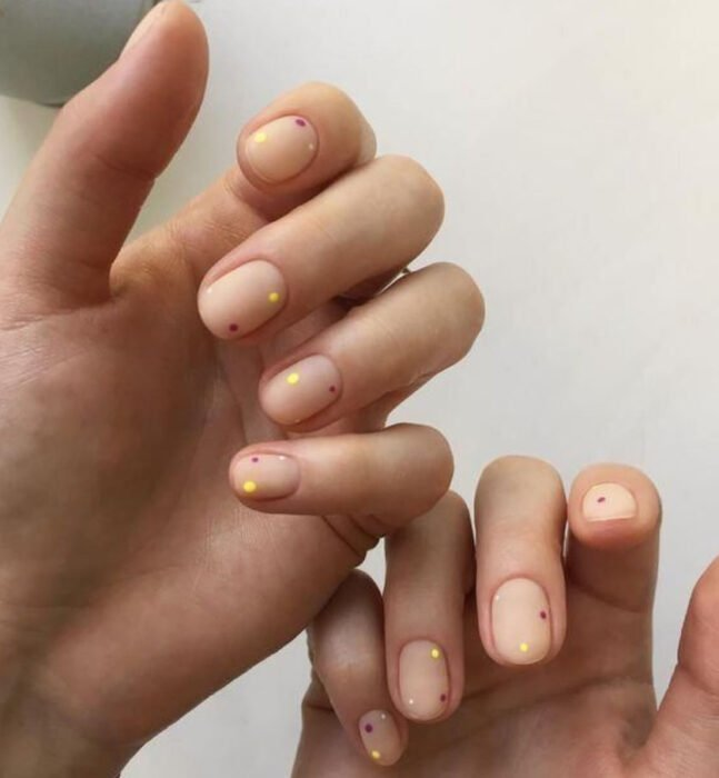 Manicure with nude background and golden dots