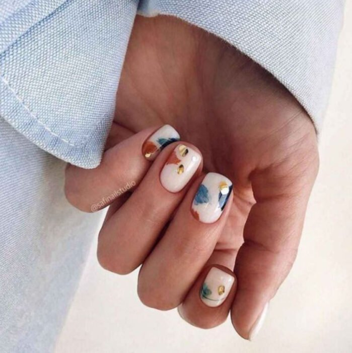 Manicure with beige background and details of brush strokes in blue, orange and yellow