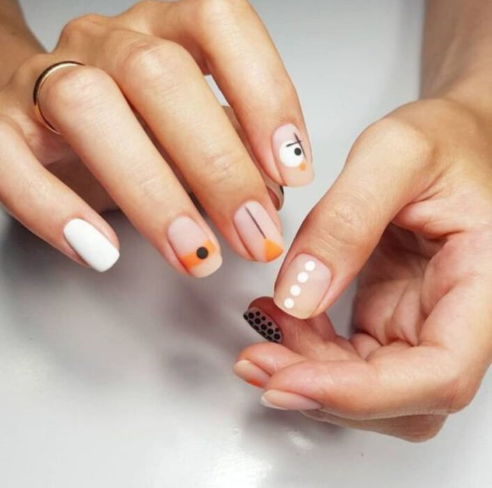 Manicure in white, orange and black